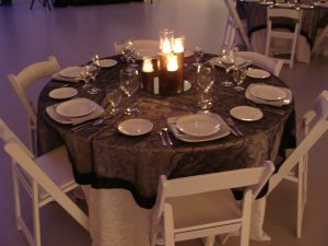 """60"""" round table with a black and white theme."""